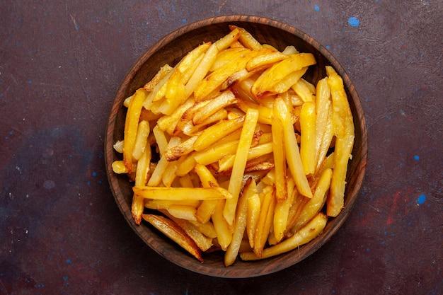 Vue de dessus des pommes de terre frites savoureuses frites à l'intérieur de la plaque sur la surface sombre