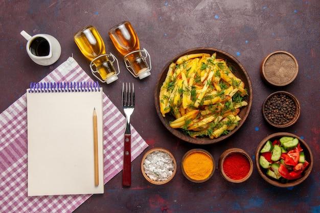 Vue de dessus des pommes de terre frites savoureuses frites avec des légumes verts et des assaisonnements sur un bureau sombre