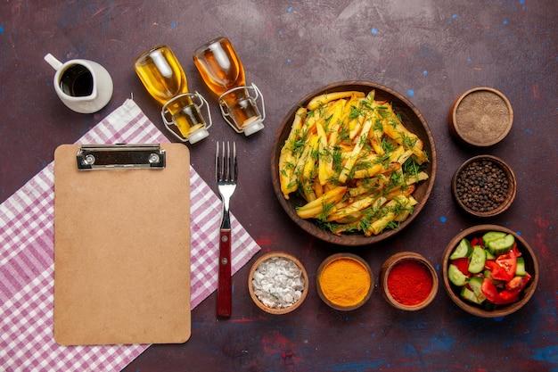 Vue de dessus des pommes de terre frites savoureuses frites avec des légumes verts et des assaisonnements sur la surface sombre