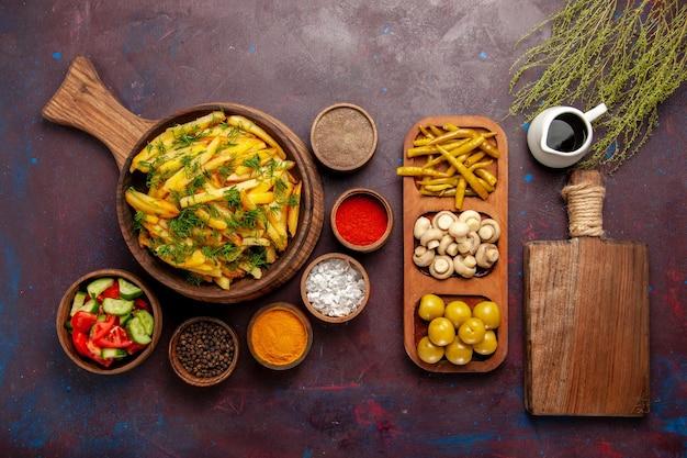 Vue de dessus des pommes de terre frites savoureuses frites avec des légumes verts et différents assaisonnements sur une surface sombre