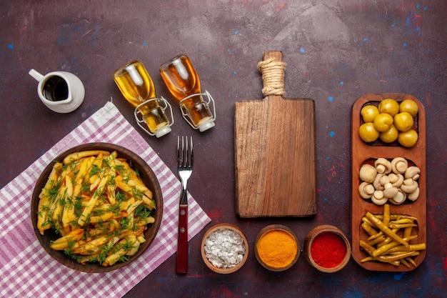Vue de dessus des pommes de terre frites savoureuses frites avec des légumes verts et de l'huile sur le bureau sombre