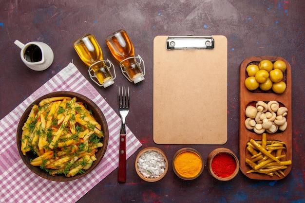 Vue de dessus des pommes de terre frites savoureuses frites avec des légumes verts et de l'huile sur la surface sombre