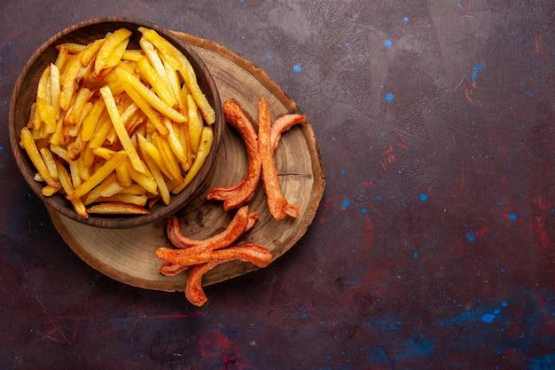 Vue de dessus des pommes de terre frites savoureuses frites avec des saucisses sur un bureau sombre
