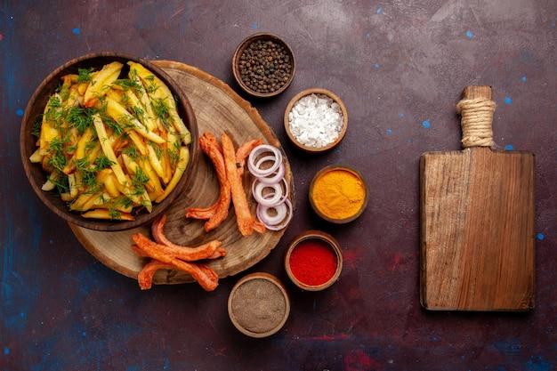 Vue de dessus des pommes de terre frites savoureuses frites avec des saucisses et différents assaisonnements sur une surface sombre