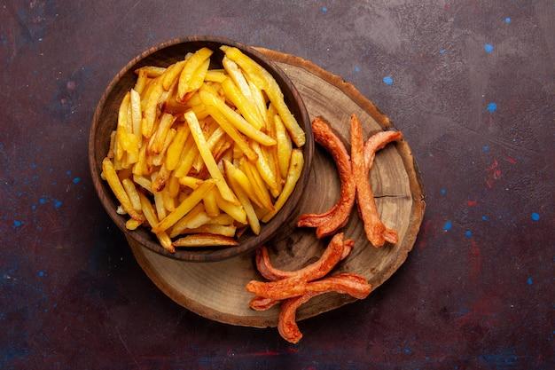 Vue de dessus des pommes de terre frites savoureuses frites avec des saucisses sur une surface sombre