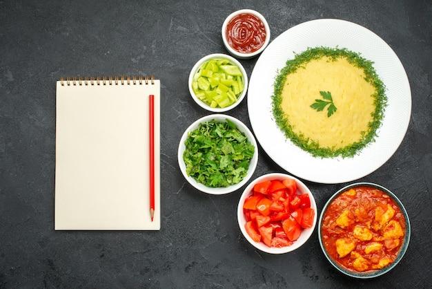 Vue de dessus des pommes de terre en purée avec des verts et des tomates sur gris