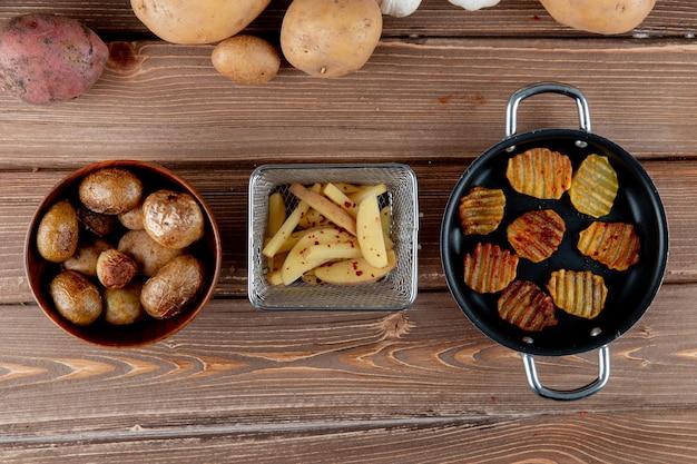 Vue de dessus de pommes de terre en tranches cuites au four avec des croustilles sur fond de bois avec copie espace