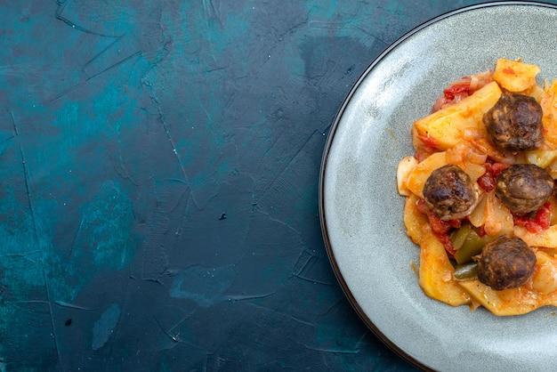 Vue de dessus pommes de terre en tranches cuites avec des boulettes de viande à l'intérieur de la plaque sur fond bleu foncé.