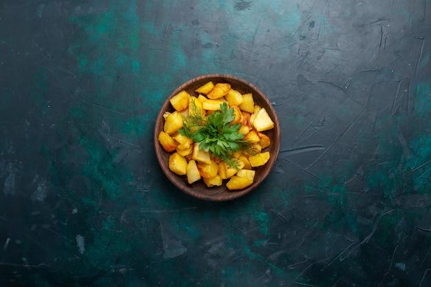 Vue de dessus pommes de terre en tranches cuites avec des verts à l'intérieur de la plaque brune sur une surface bleu foncé