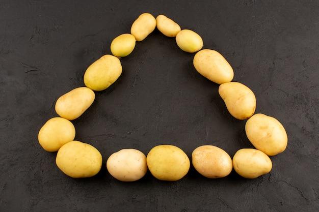Vue de dessus des pommes de terre triangle entier en forme sur le fond sombre