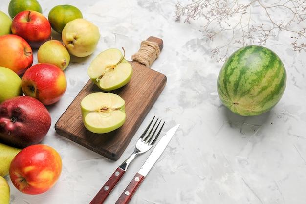Vue de dessus des pommes vertes avec d'autres fruits sur fond blanc clair