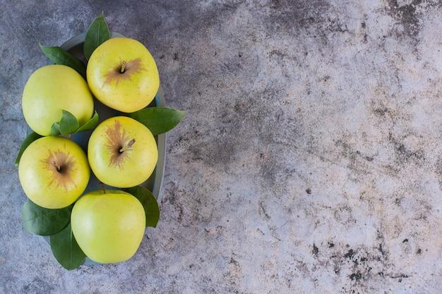 Vue de dessus des pommes vertes biologiques sur fond gris.