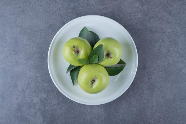 Vue de dessus des pommes vertes biologiques fraîches sur plaque blanche