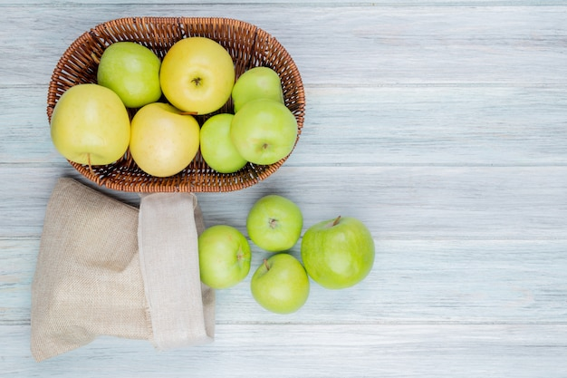 Vue de dessus des pommes vertes débordant de sac et panier de pommes sur table en bois avec espace copie