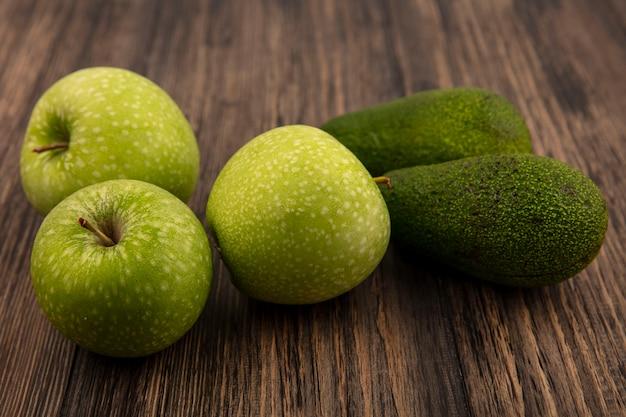 Vue de dessus des pommes vertes fraîches avec des avocats isolés sur un mur en bois
