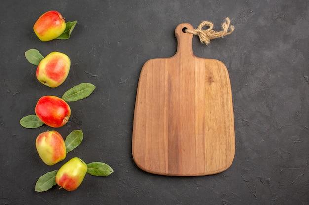 Vue de dessus pommes vertes fraîches avec des feuilles vertes sur table sombre arbre moelleux frais mûrs