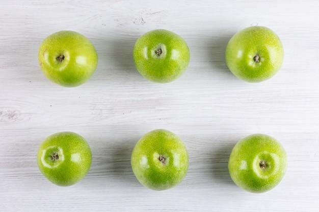 Vue de dessus des pommes vertes sur horizontal en bois blanc