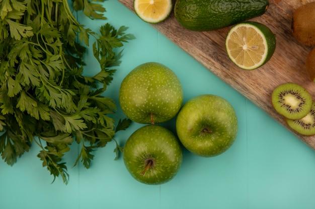 Vue de dessus des pommes vertes saines avec des avocats limes et des kiwis sur une planche de cuisine en bois sur un mur bleu