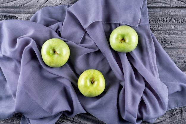 Vue de dessus des pommes vertes sur tissu gris sur horizontal en bois gris