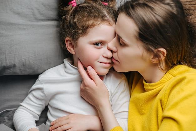 Vue de dessus portrait d'heureuse jeune mère embrassant mignon petit enfant fille étreignant la liaison allongée sur le lit, jeune maman aimante et joyeuse rire passer du temps ensemble à la maison