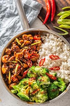 Vue de dessus portrait d'un poulet teriyaki fini avec du riz et du brocoli cuit à la vapeur dans une casserole. piment frais et poireaux à part.