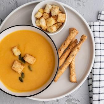 Vue de dessus de potiron, soupe à la crème de carottes dans un bol. avec croûtons, graines de citrouille et bâtonnets de pain.