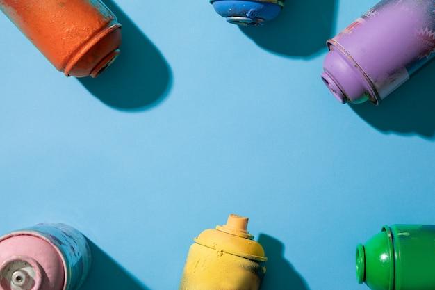 Vue de dessus des pots de peinture en aérosol sur fond bleu avec espace libre pour le texte