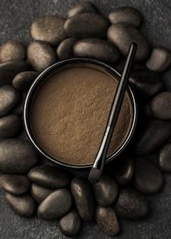 Vue de dessus de la poudre fine dans un bol avec pinceau et pierres