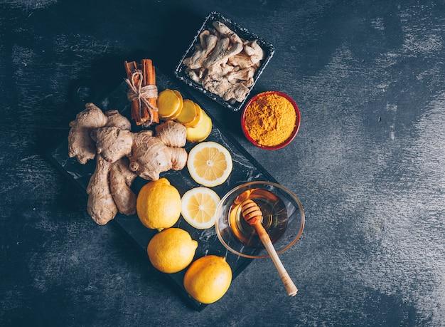 Vue de dessus de poudre de gingembre avec du gingembre, du citron, du miel et de la cannelle sèche sur fond texturé foncé. horizontal