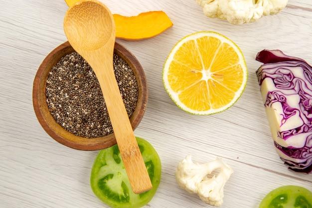 Vue de dessus en poudre de poivre noir dans un petit bol cuillère en bois couper les légumes sur une table en bois blanc