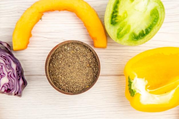 Vue de dessus de la poudre de poivre noir dans un petit bol de légumes coupés sur une table en bois blanc