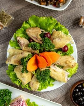 Vue de dessus de poulet bouilli aux herbes sur une feuille de laitue avec des tranches de carotte