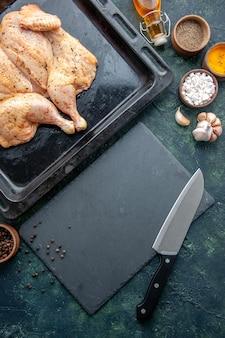 Vue de dessus poulet épicé frais avec des assaisonnements sur fond bleu foncé alimentaire plat de poivre épices dîner couleur de la viande sel