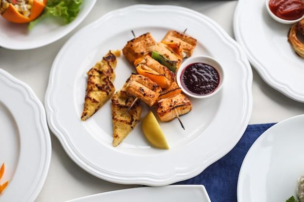 Vue de dessus poulet grillé sur brochettes avec légumes citron et sauce sur une assiette