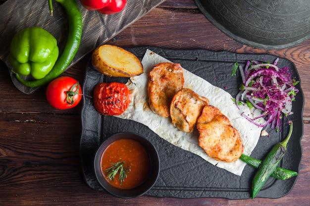 Vue de dessus poulet grillé avec pain pita, tomate, oignon, poivron et sauce horizontale