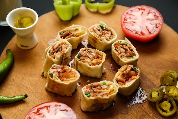 Vue de dessus poulet haché doner dans du pain pita avec des tomates et des poivrons sur un support