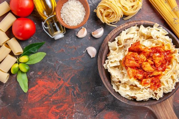 Vue de dessus de poulet avec plat de pâtes de pâte sur un plat de pâtes sombre surface sombre