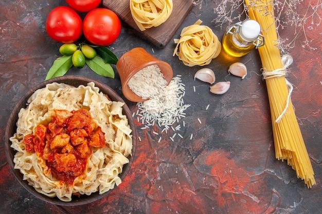 Vue de dessus poulet avec plat de pâtes de pâte avec des tomates sur un repas de pâtes de pâte de surface sombre