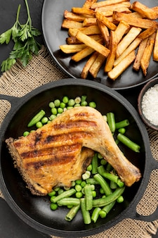 Vue de dessus de poulet et de pois cuits au four dans une casserole avec des pommes de terre