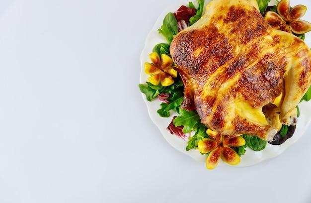 Vue de dessus poulet rôti sur plaque blanche avec salade et figues sur mur isolé blanc.