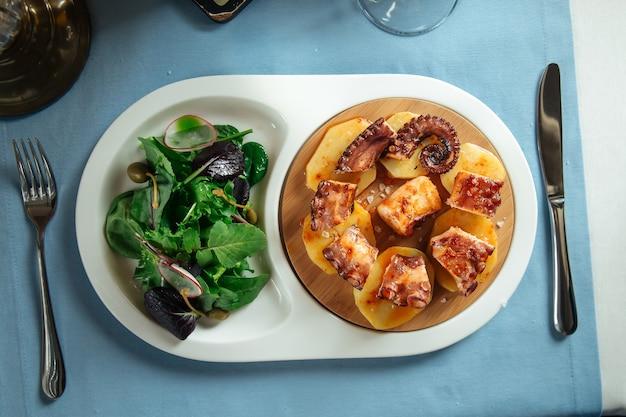 Vue de dessus sur le poulpe plat national espagnol en galicien avec salade de légumes verts