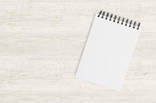 Vue de dessus pour des affaires. cahier vierge pour peindre, dessiner et dessiner sur une texture en bois.