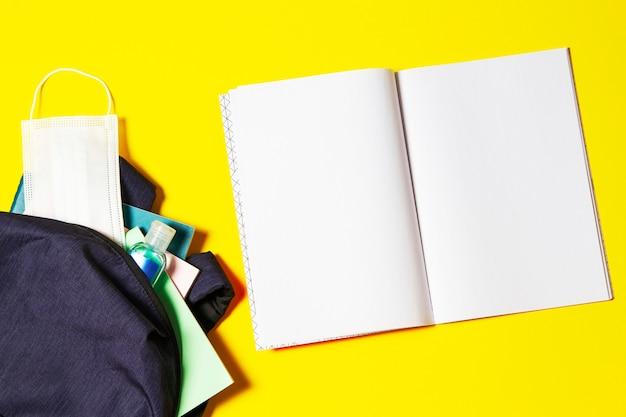 Vue de dessus pour ouvrir le sac à dos avec des cahiers, des fournitures scolaires, un désinfectant pour les mains et un masque médical de protection sur fond jaune
