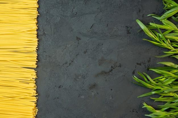 Vue de dessus pour les spaghettis crus et l'estragon frais avec copie espace au milieu sur du béton noir