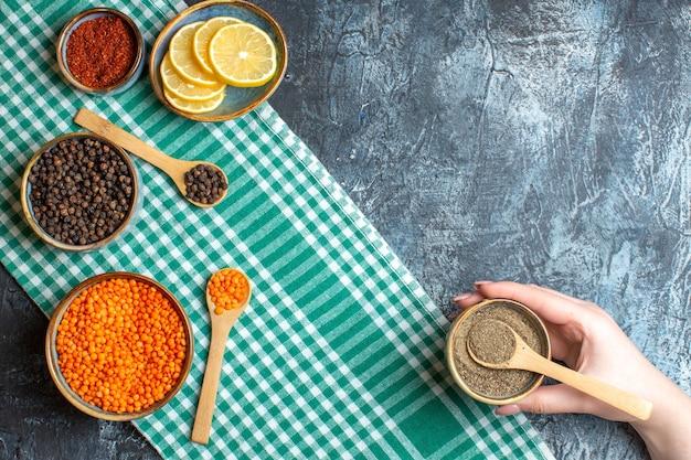 Vue de dessus de la préparation du dîner avec différentes épices pois jaunes sur une serviette verte sur une table sombre