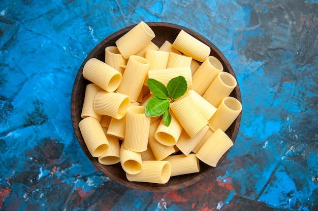 Vue de dessus de la préparation du dîner avec des nouilles de pâtes au vert dans un pot marron sur fond bleu
