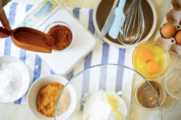 La vue de dessus prépare la nourriture des ingrédients pour faire des aliments sucrés brownie en vérifiant le poids pour cuisiner.
