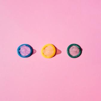 Vue de dessus des préservatifs colorés sur fond rose