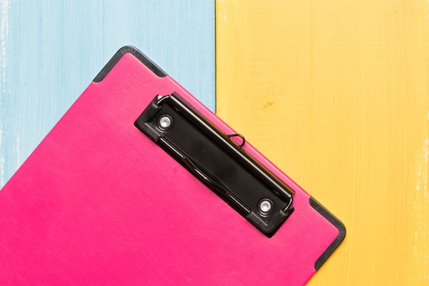 Vue de dessus de presse-papiers rose sur des arrière-plans colorés avec espace copie pour le texte