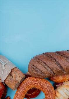 Vue de dessus des produits de boulangerie comme bagel brioche pain baguette croustillante et pain noir sur fond bleu avec espace copie